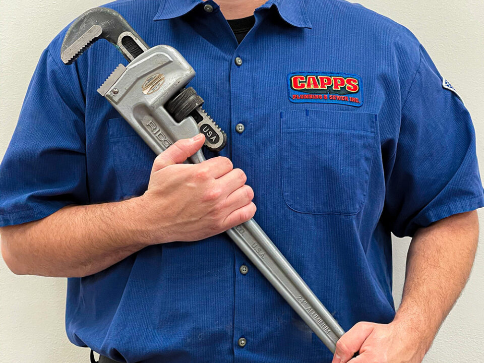 A CAPPS technician holding a large wrench.